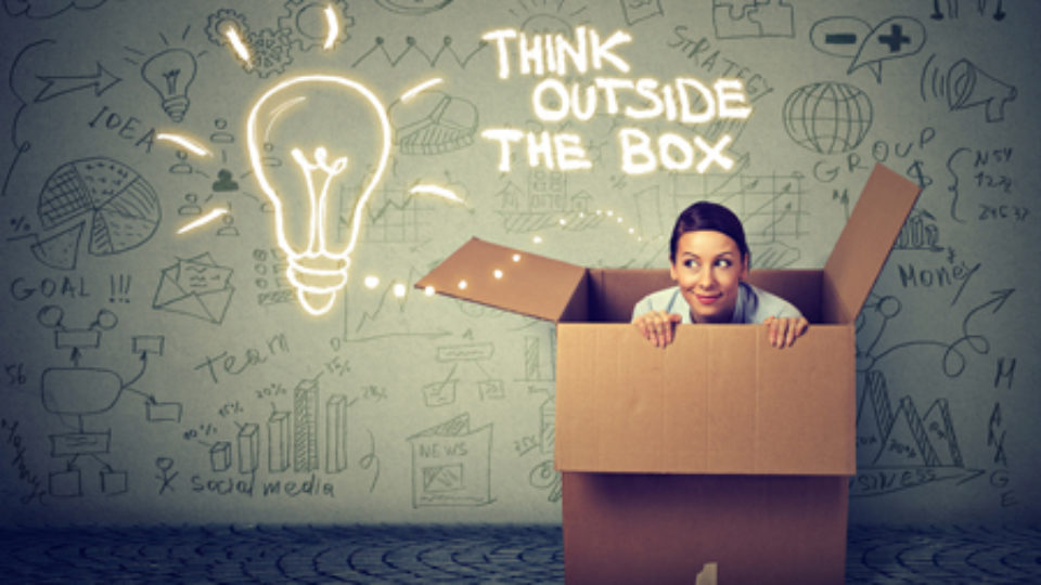 Think outside box concept. Young woman coming out of box