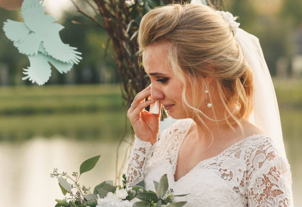 Gorgeous bride cries standing before arch made of woven branches