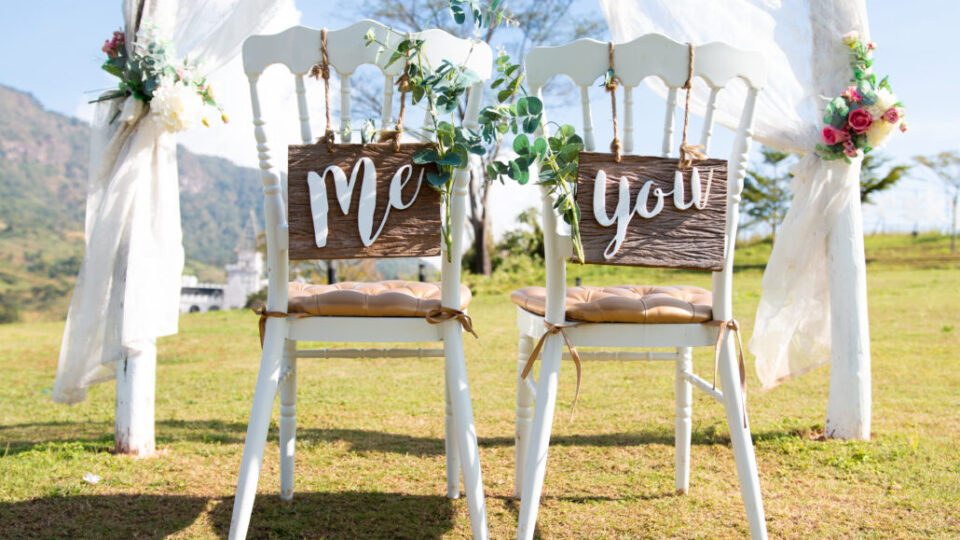 Wedding Me and You signs on chairs standing in the woods.